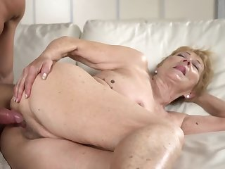 A nasty old granny gets a hard dick between her legs on the sofa